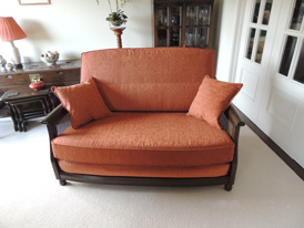 An Ercol 2-seater sofa re-upholstered in a bright orange chenille fabric