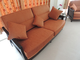 An Ercol 3-seater sofa re-upholstered in a bright orange chenille fabric