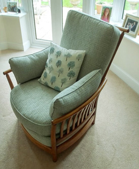 An Ercol armchair transformed with a green fabric and matching scatter cushions