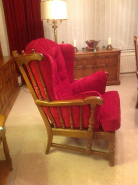 A re-upholstered Ercol armchair in a red fabric